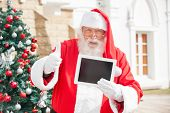 Portrait of Santa Claus gesturing thumbsup while holding digital tablet outside house