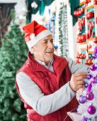Senior male owner in Santa hat decorating Christmas tree at store