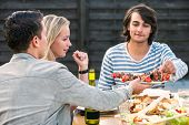 Two young men and woman enjoying a dinner party outside