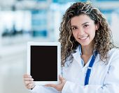 Female doctor holding a tablet computer and showing screen