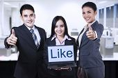 stock photo of enthusiastic  - Group of business people showing like on laptop and thumbs up - JPG