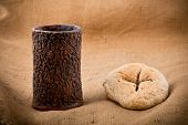 stock photo of chalice  - still life with chalice and bread on the textile tablecloth - JPG