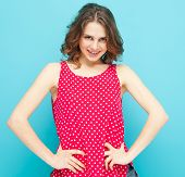 Beautiful Girl In A Red Blouse With Polka Dots On A Blue Background, In Soft Focus