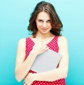 foto of woman red blouse  - beautiful girl in a red polka dot blouse with a diary on a blue background