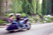 two bikers on mountain highway, riding around a curve with a motion blur