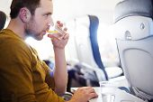 Man in the aircraft is drinking water