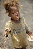 KOLMINY, HAITI - FEBRUARY 12, 2014.  A malnourished preschooler eating peanut butter bread received
