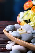 Composition with  spa stones and candles in wooden bowl, near flowers on bright background