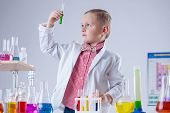 Cute boy looking at color of reagent in test-tube
