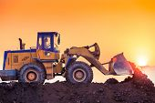 stock photo of wheel loader  - heavy wheel excavator machine working at sunset - JPG