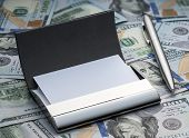 Business card holder and pen on the background of the new hundred dollars American