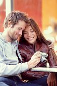 Happy young couple looking at pictures on camera. Beautiful young lovers having fun together outside