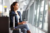 stock photo of terminator  - Passenger traveler woman in airport waiting for air travel using tablet smart phone - JPG