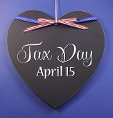 Tax Day, April 15, Reminder Greeting Message With Usa Ribbon On A Heart Shaped Blackboard Against A
