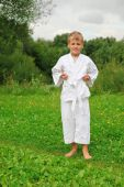 stock photo of karate kid  - karate boy stands on lawn - JPG
