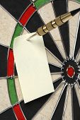Dartboard with dart and blank note