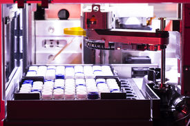 image of hplc  - HPLC autosampler in a real laboratory lit with red gel vials in rack - JPG
