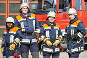 image of fire brigade  - firefighter crew in uniform in front of fire engine machine and fireman team - JPG