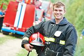 stock photo of firemen  - young smiling fireman firefighter in uniform in front of fire engine machine - JPG