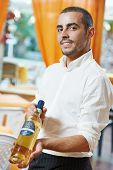 Male waiter sommelier steward sugesting wine bottle in restaurant