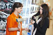 Young woman choosing electric hairdryer in home appliance shopping mall supermarket