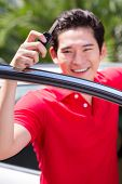 Asian man showing key of his new car