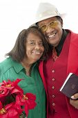 Portrait of a happy senior couple dressed in red, green and white.  She carries a pot of poinsettias