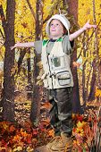 An adorable kindergarten explorer standing with arms spread wide, happily looking up at the beautiful fall colors surrounding her.