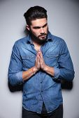 Handsome man with beard in blue shirt praying