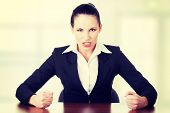 Angry businesswoman at the desk, isolated on white background