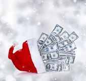 Dollar banknotes coming out of Santa Claus hat