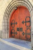 picture of entryway  - Gorgeous old wood doors, with imposing black hardware and handles, at entryway of stone building.