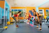 Girls in fitness club exercising with dumbbells