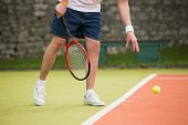 Young tennis player about to serve on a sunny day