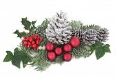 Christmas and winter decoration  with holly, snow, red baubles, mistletoe, fir and cedar leaf sprigs