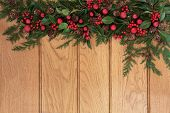 Christmas and winter background border with red bauble decorations, holly and cedar cypress with pin