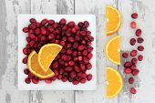 Cranberry and orange fruit over weathered wooden white background.