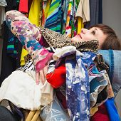 pretty young woman with a pile of clothes in his hands