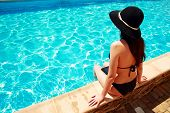 Back view portrait of a woman sitting on the ledge of the pool
