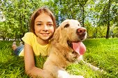 Teenage girl with her dog laying in park