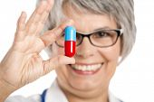 Happy old female doctor holding a a big pill, isolated on white