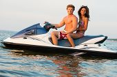 image of ski boat  - Multi ethnic couple sitting on a jet ski - JPG