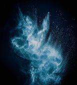 Blue powder exploding isolated on black