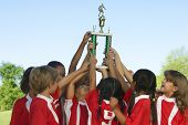 Group of children holding trophy above heads