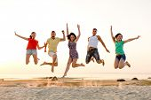friendship, summer vacation, holidays, party and people concept - group of smiling friends dancing a