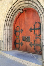 foto of entryway  - Gorgeous old wood doors, with imposing black hardware and handles, at entryway of stone building. ** Note: Soft Focus at 100%, best at smaller sizes - JPG