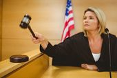 Judge about to bang gavel on sounding block in the court room