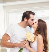 Young man giving girlfriend white roses at home in the kitchen