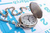 Silver pocket clock on calendar background