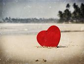 Vintage photo of red heart on exotic sandy beach - Valentine's day concept